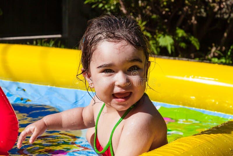 Милый, счастливый, усмехаясь ребёнок малыша, играя в красочное раздувном стоковое изображение
