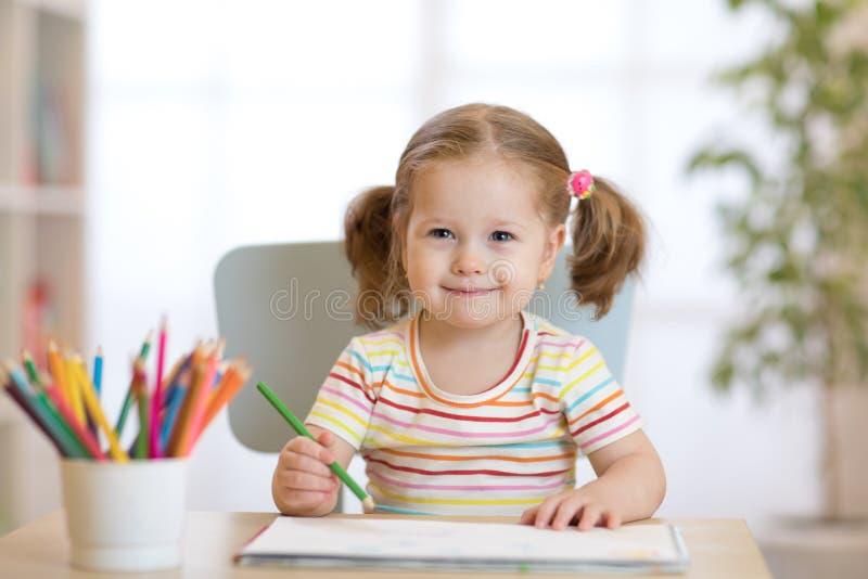 Милый счастливый чертеж девушки маленького ребенка с карандашами в детском саде стоковая фотография rf