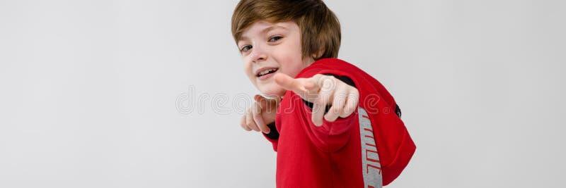Милый уверенно кавказский маленький усмехаясь мальчик в красном свитере указывая его палец на камере на серой предпосылке стоковое фото rf