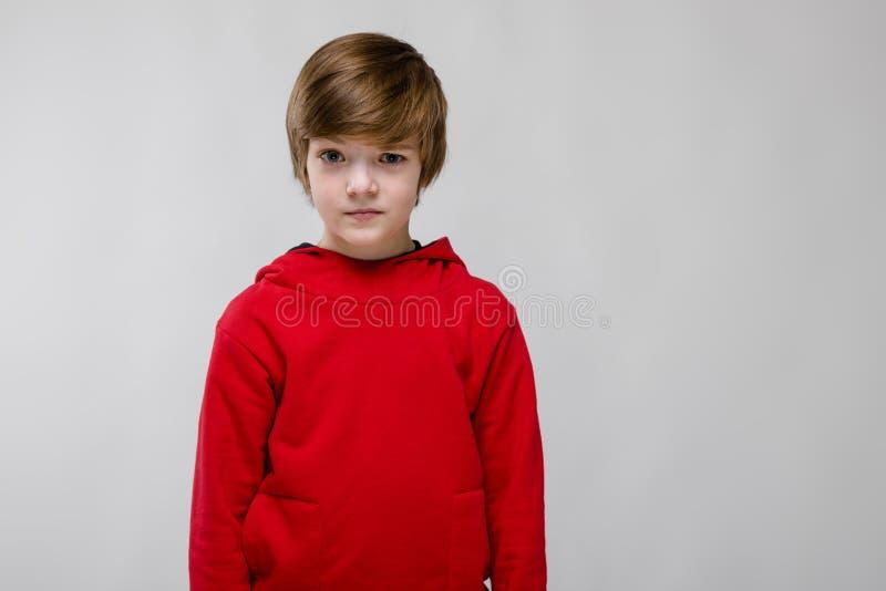 Милый уверенно маленький кавказский мальчик в красном свитере на серой предпосылке стоковые изображения rf