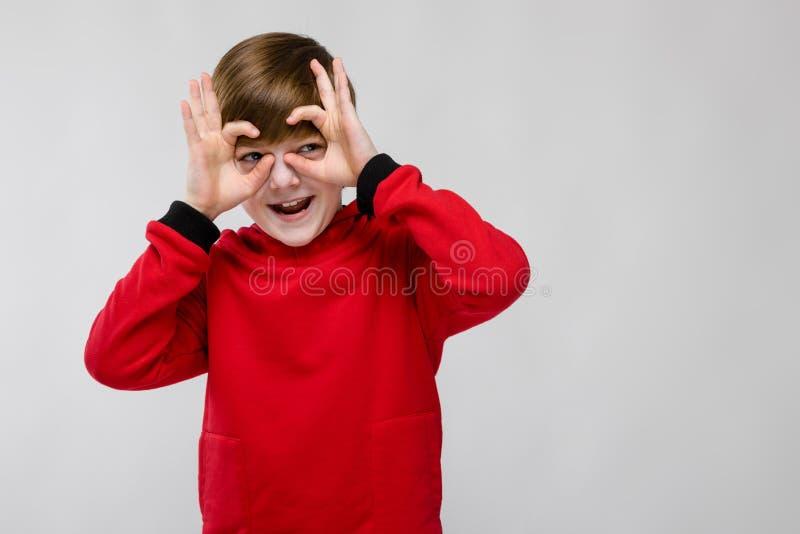 Милый уверенно маленький кавказский мальчик в красном свитере околпачивая показывать на серой предпосылке стоковые изображения rf
