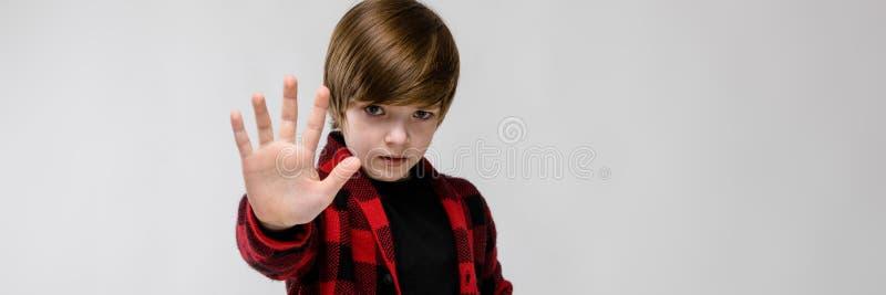 Милый уверенно унылый маленький кавказский мальчик в checkered знаке стопа показа рубашки на серой предпосылке стоковое фото