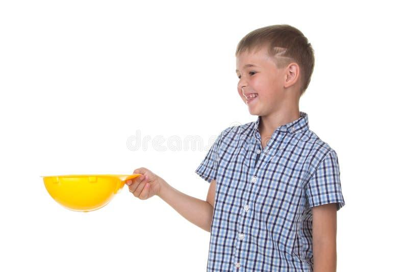 Милый усмехаясь мальчик в рубашке ключа checkered держа шлем здания над белизной изолировал предпосылку, половинное тело стоковая фотография rf