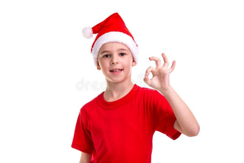 Милый усмехаясь мальчик, шляпа santa на его голове, показывая в порядке знак Концепция: рождество или С Новым Годом! праздник стоковое изображение