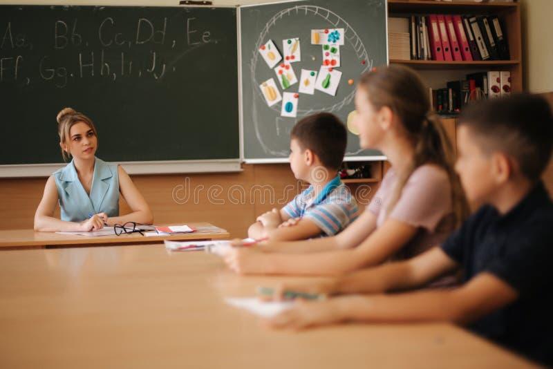 Милый учитель в классе сидя на столе и спрашивая детям образование, начальная школа, учить и люди стоковое изображение rf