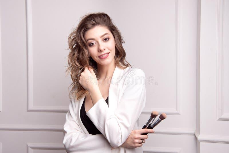 Милый художник макияжа брюнета используя щетку макияжа стоковые фотографии rf