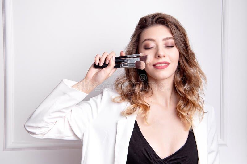 Милый художник макияжа брюнета используя щетку макияжа стоковое изображение