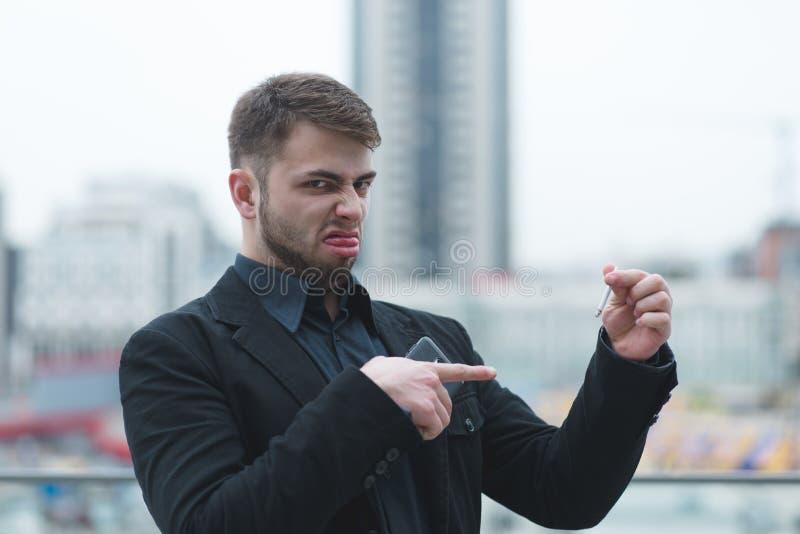 Милый человек не любит сигареты Человек держит сигарету в его оружиях и завивает Сигарета зла стоковое изображение rf