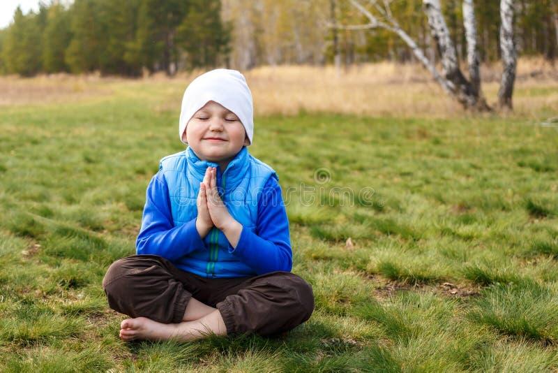 Милый четырехклассный мальчик сидит на зеленой траве стоковые изображения