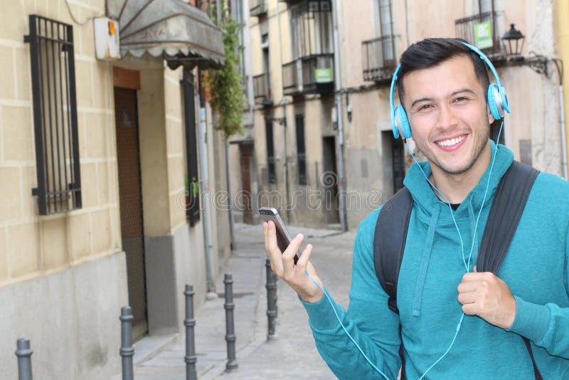 Милый этнический молодой мужчина используя его смартфон для того чтобы слушать побитый outdoors с космосом экземпляра стоковые фото