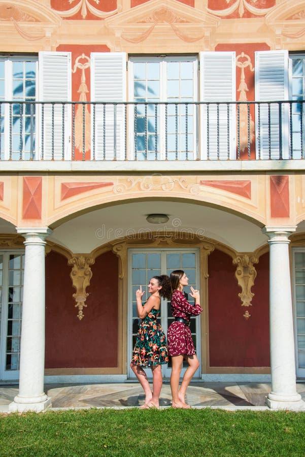 2 милых девушки делают представление Жамес Бонд стоковое фото