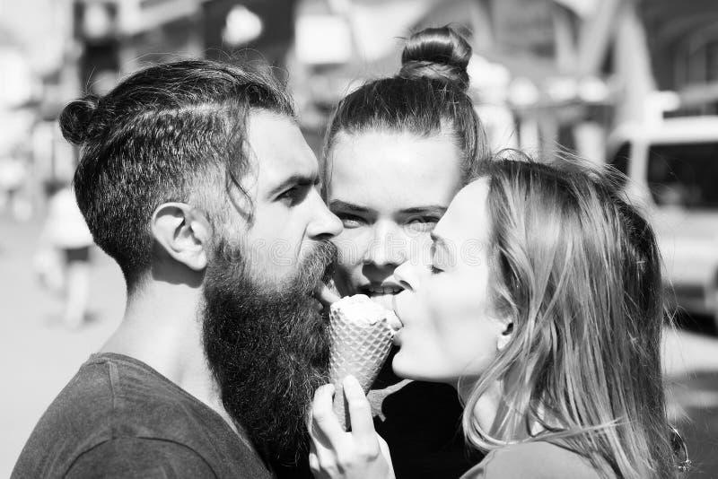 2 милых девушки и зверского, бородатого человек лижа мороженое стоковое фото