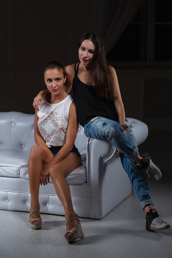 2 милых девушки представляя в студии стоковое фото rf
