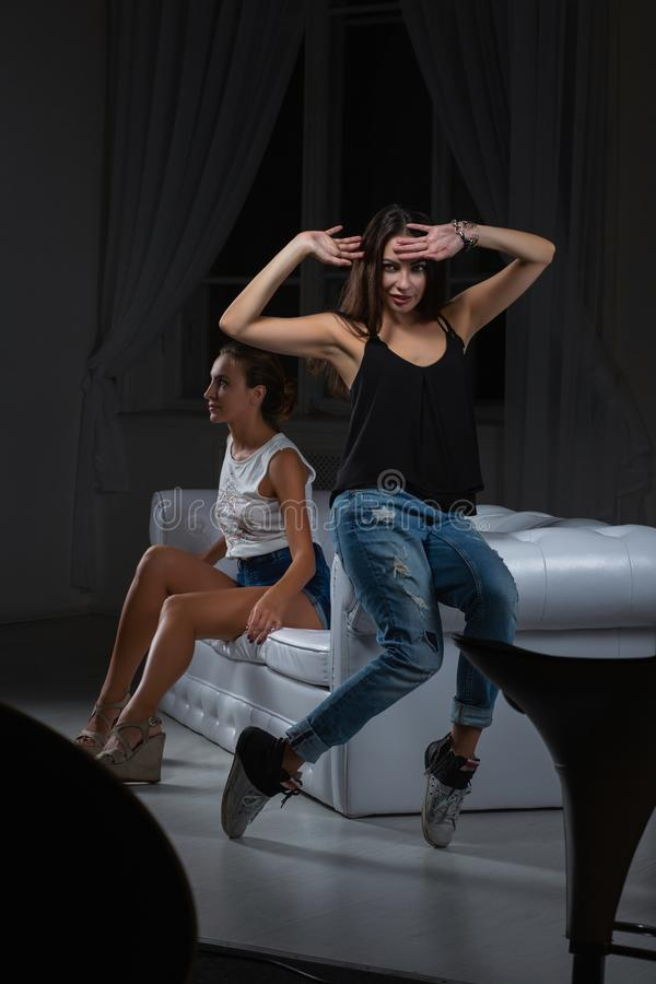 2 милых девушки представляя в студии стоковая фотография