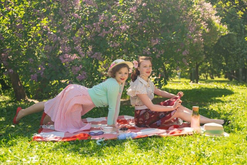 2 милых подруги сидя на красном одеяле на зеленой траве и иметь пикник лета счастливая женщина имея остатки и потеху дальше стоковое изображение