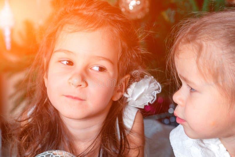 2 милых сестры такой же лож возраста рядом с деревом Нового Года одно стоковые фотографии rf