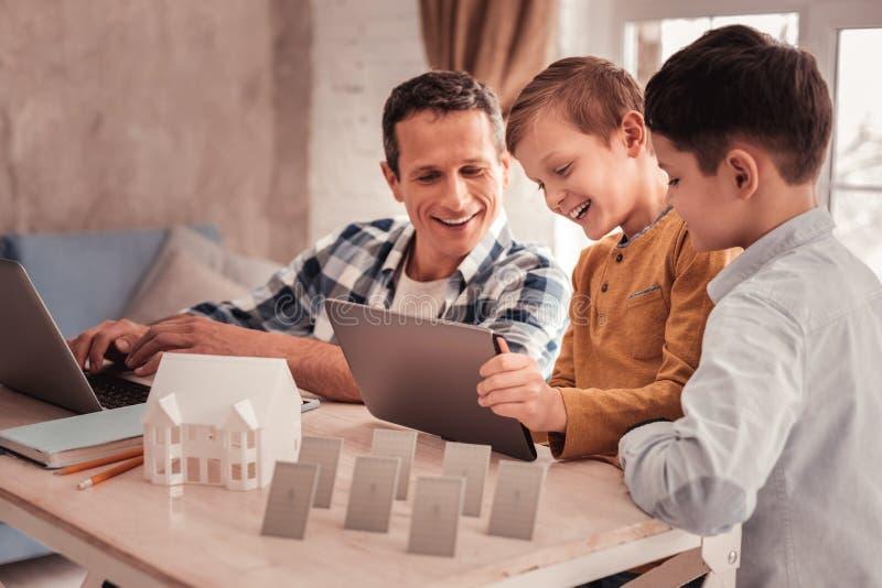 2 милых сынов делая план энергии для их будущего дома с отцом стоковое фото