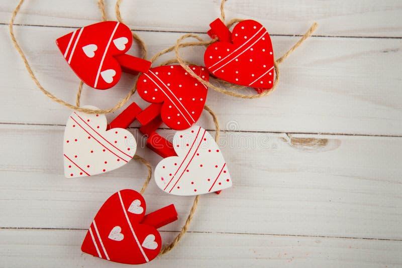 6 милых украшенных сердец как зажимки для белья кладя на белый деревянный стол Взгляд сверху, космос для текста стоковое фото