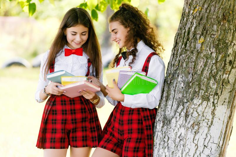 2 милых школьницы в стойке школьной формы с книгами outdoors в парке стоковая фотография rf