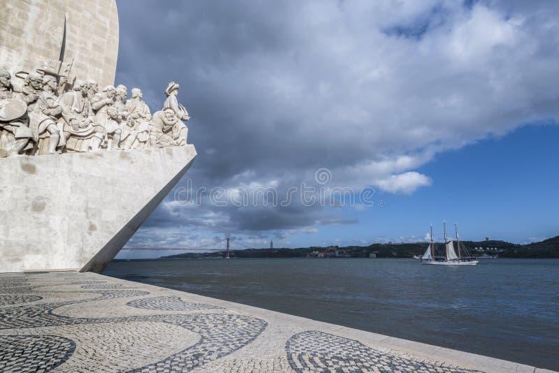 Мимолетный взгляд памятника открытиям и моста 25-ое апреля на реке Тахо в Лиссабоне стоковая фотография rf