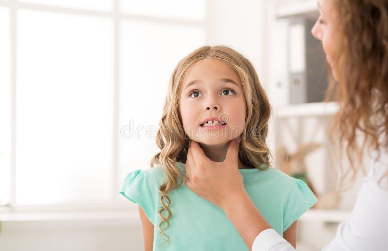 Миндалины девушки женского доктора рассматривая в больнице стоковые изображения rf