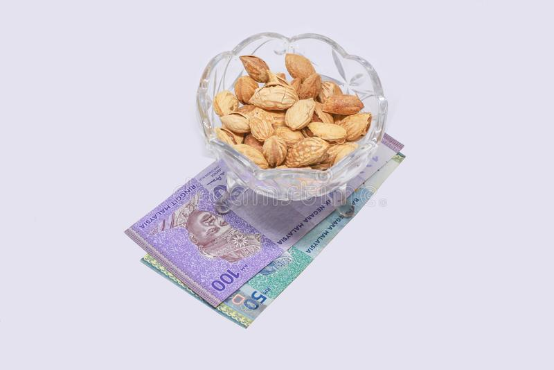 Миндалины с деньгами и белой предпосылкой стоковая фотография