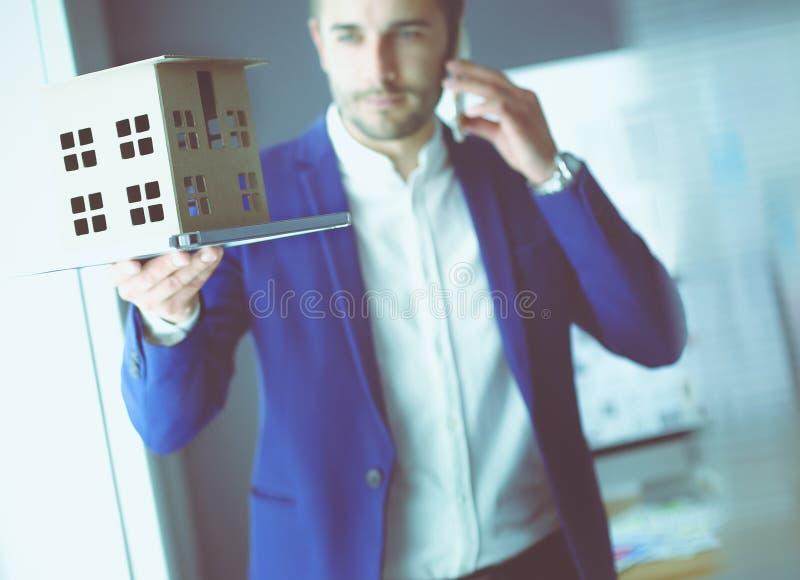 Миниатюра дома удерживания бизнесмена в наличии стоя в офисе стоковое фото