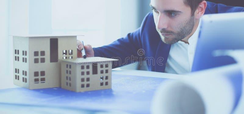 Миниатюра дома удерживания бизнесмена в наличии стоя в офисе стоковое фото rf