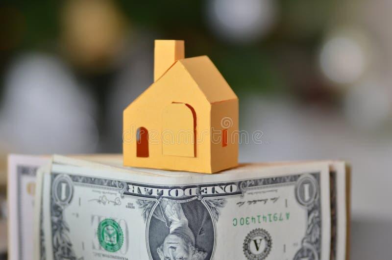 Миниатюрная бумага сделанная дом стоять на деньгах стоковое фото