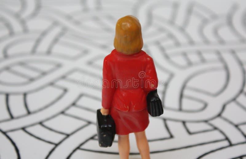 Миниатюрная женщина в красном пальто от позади внутри лабиринта Потерянная или смущенная дама решает, который путь пойти стоковая фотография
