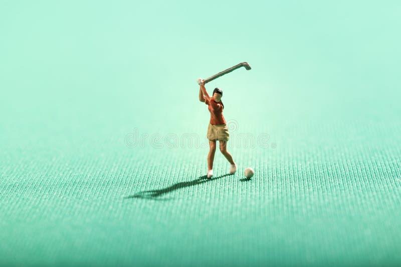 Миниатюрная женщина играя гольф на зеленом цвете стоковое изображение