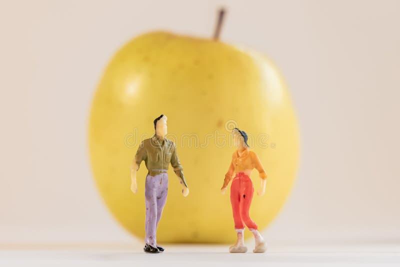 Миниатюрная женщина и мужчина стоят рядом с большим желтым яблоком Уменьшить глубину фона поля Здравоохранение, здоровье стоковое фото rf