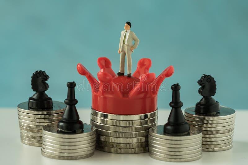 Миниатюрная диаграмма бизнесмен стоя на красном короле кроны с st стоковая фотография