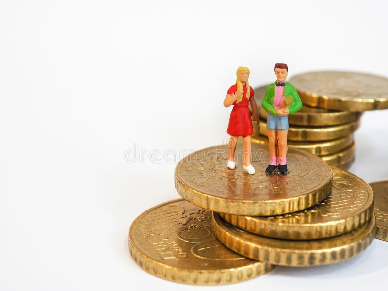 Миниатюрная стойка детей на монетках евро План денег семьи будущий стоковое фото