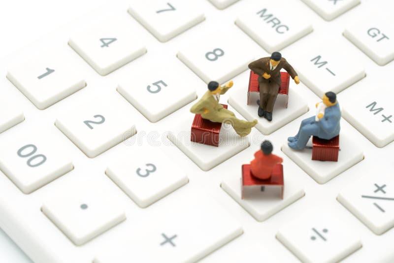 Миниатюрное 4 человек сидя на красных штапелях помещенных на белом калькуляторе встреча или обсуждение как концепция дела предпос стоковая фотография