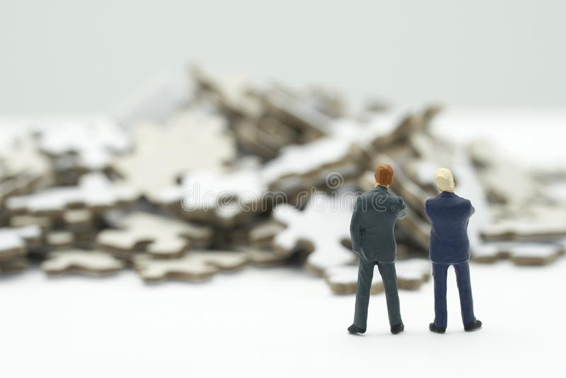 Миниатюрные бизнесмены людей стоя финансовый анализ или вклад внутри разрешают головоломки для того чтобы найти решение дела испо стоковое фото rf