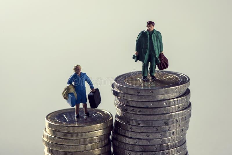 Миниатюрные женщина и человек на кучах евро чеканят стоковое изображение