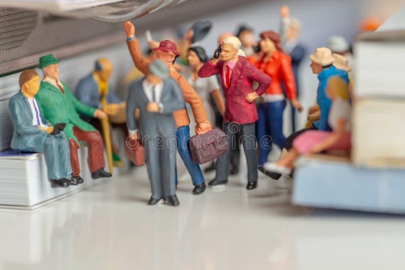 Миниатюрные игрушки человека и женщины с мобильными телефонами говоря в концепции общественного транспорта средней стоковые изображения