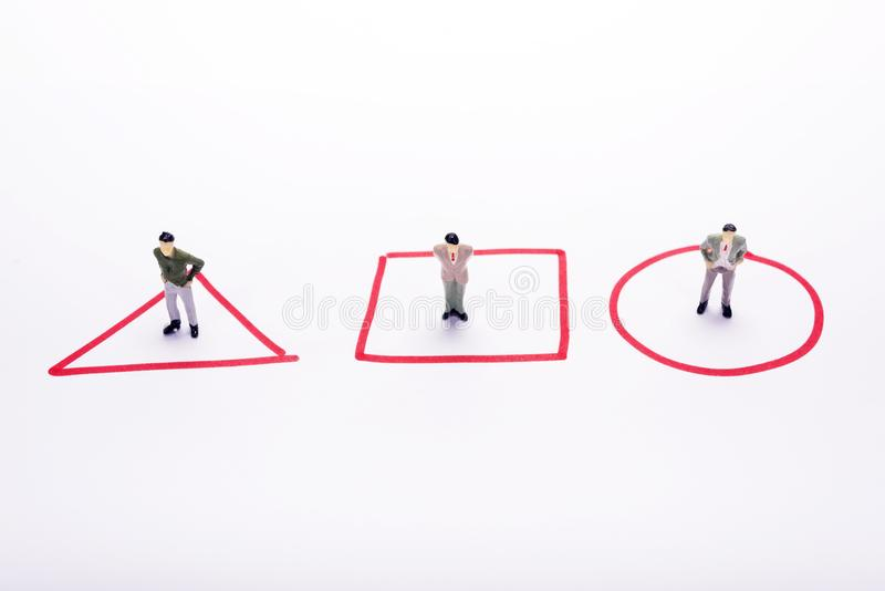 Миниатюрные люди 3 бизнесмена стоя в красном цвете diagrams ove стоковое изображение rf