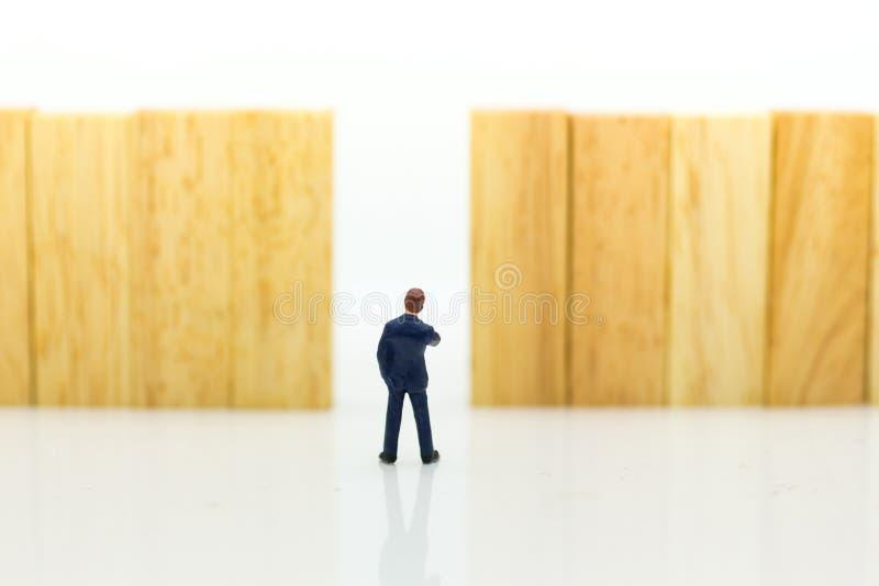 Миниатюрные люди: Бизнесмены идут к точке выхода Отображайте польза для самого лучшего выбора выберите, концепция дела стоковая фотография rf