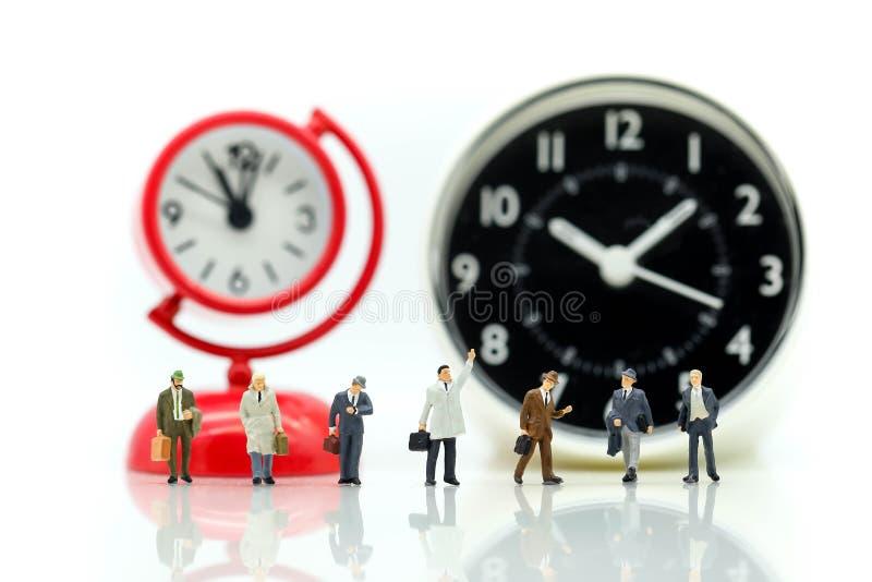 Миниатюрные люди: Бизнесмен стоя с часами, делом времени стоковое фото rf