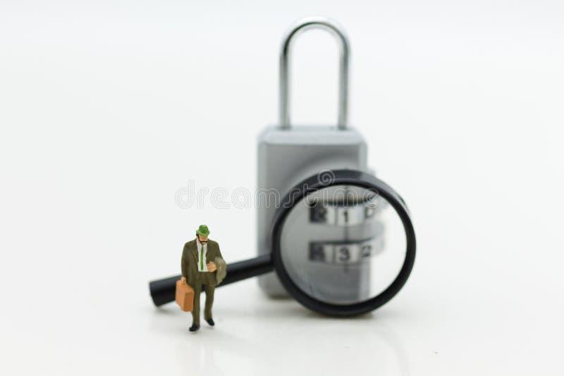 Миниатюрные люди: Бизнесмен с зашифрованием лупы и ключа для всех замков Польза изображения для системы безопасности предпосылки стоковые изображения rf