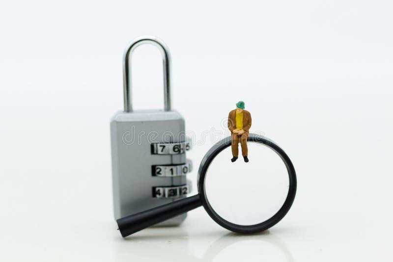 Миниатюрные люди: Бизнесмен с зашифрованием лупы и ключа для всех замков Польза изображения для системы безопасности предпосылки стоковые фото