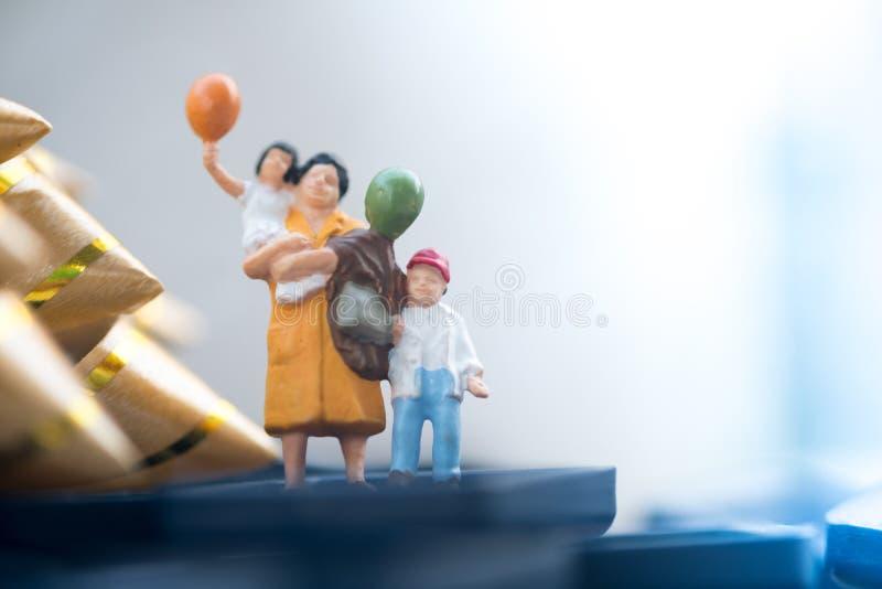 Миниатюрные люди: воздушный шар удерживания мамы и сына стоковое фото rf