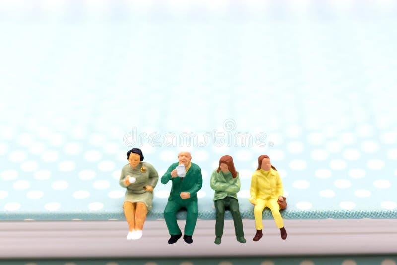 Миниатюрные люди: Команда дела сидя на книге и имея перерыв на чашку кофе Польза изображения для концепции дела стоковое фото rf