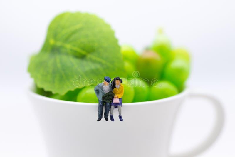 Миниатюрные люди: Пары принимают время для чашки кофе Польза изображения для концепции дела еды стоковые изображения