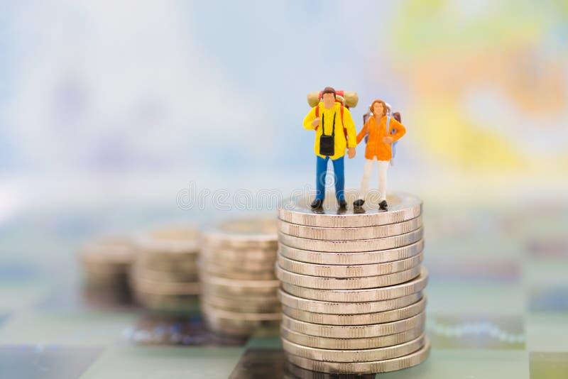 Миниатюрные люди: пары путешественника вычисляют положение na górze монеток стога используя как концепцию планирования выхода на  стоковые фото