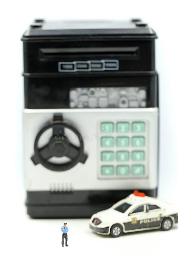 Миниатюрные люди: Полиция с уголовным похитителем раскрывает безопасные крадя деньги от банка стоковые изображения rf