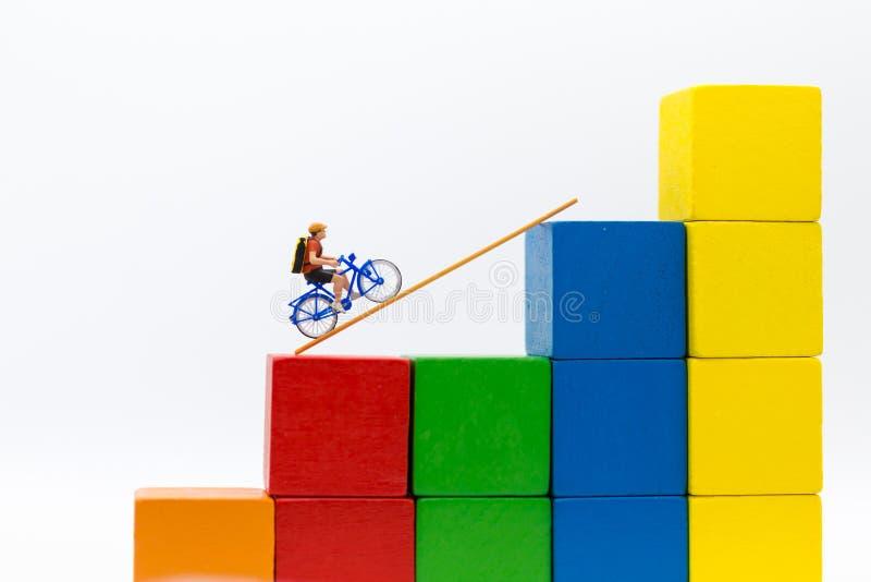 Миниатюрные люди: Польза путешественника велосипед с принимает лестницу от одного места к другим Польза изображения для перемещен стоковые изображения