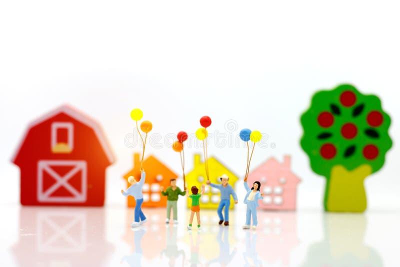 Миниатюрные люди при семья держа воздушный шар с домами, счастливыми стоковое изображение rf